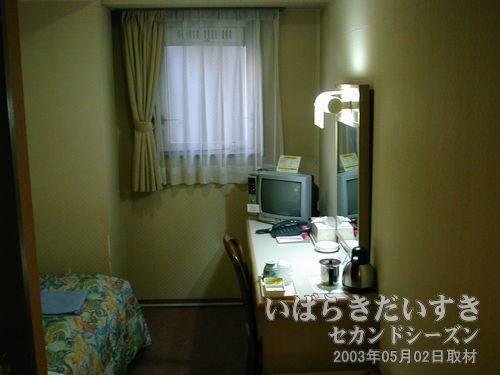 部屋に入る<br>テーブルとテレビとベッド、左手手前にはユニットバスがあります。一般的な構成の部屋です。