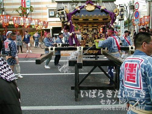 神輿に水を掛ける<br>神輿の結束されている綱に水を掛けています。縄がほどけないようにするためでしょう。