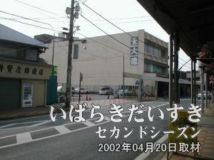 土浦駅西口からのびる通りを歩き、高架道路をくぐりさらに歩いていくと、商店街が続きます。 その一角に大徳屋の名前が見える建物があり、その手前の駐車場が、土浦京成百貨店跡地です。