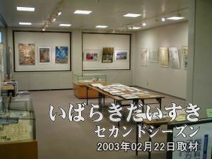 資料展 展示コーナー<br>展示コーナーのブースでは、左手に書籍、中央手前が関係者用資料。中央奥がグッズ。右と奥の壁にはポスターが展示されています。