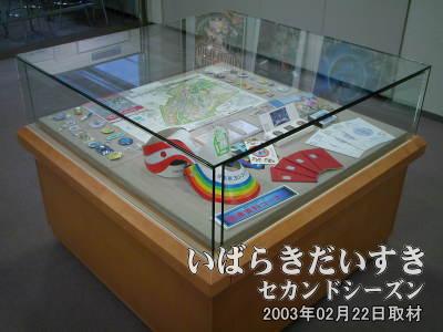 ショーケースの中には「万博会場の地図」、「ワッペン(バッチ)」、「メダル」、「シール」、「紙製の帽子」などが展示されています。 2000年夏に、つくばエキスポセンター(茨城県つくば市)で行なわれた『科学万博15周年記念 特別展示展(つくば訪問道中記14)』でも展示されていたような資料がたくさん並べられています。