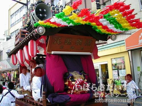 東崎町の山車<br>おもちゃ屋の前で待っているのは、東崎町の山車、赤い獅子頭が置かれています。