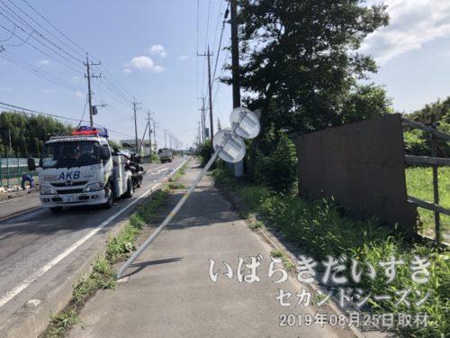 曲がった標識と、回収される大破した車。
