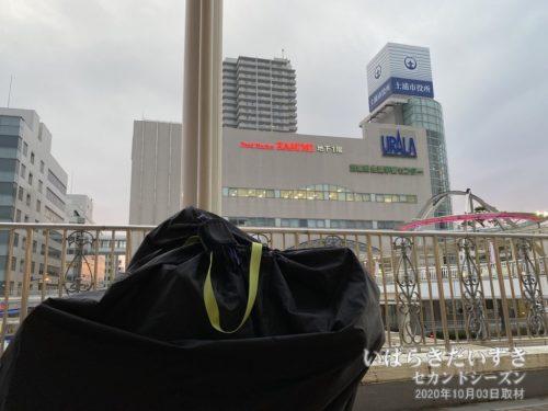 自転車を輪行袋に収納。後ろは土浦市役所。