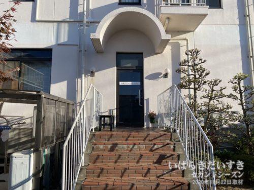 ホテル裏手入口。写真左手にある洗濯機は、フロントにお金を払い使用します。
